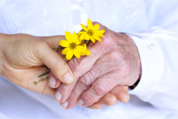 caregiver and elder hand in hand